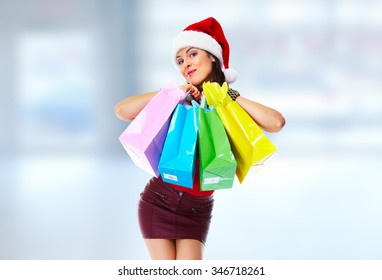Santa helper christmas girl with  shopping bags over blue background.