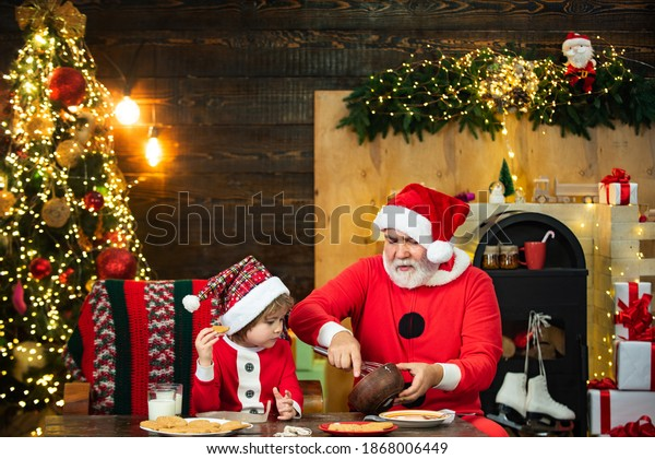 Santa helper. Happy father and son in Santa hat with cookies have a Christmas. Christmas interior. Happy new year. Christmas Celebration holiday