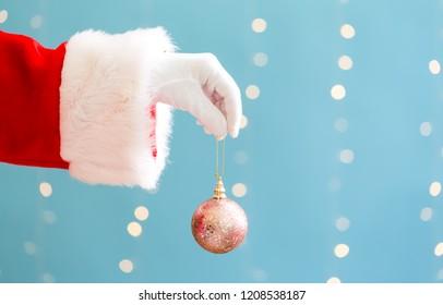 Santa holding a Christmas bauble on a shiny light blue background