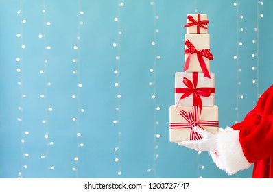 Santa holding Christmas gift boxes on a shiny light blue background
