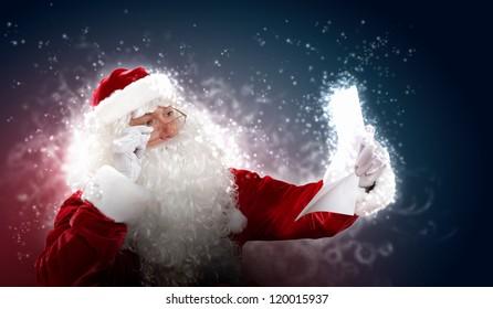 Santa holding Christmas letters and looking at camera