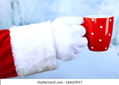 Santa holding mug in his hand, on light background
