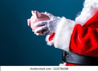 Santa holding a piggy bank on a dark blue background