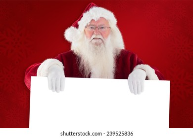Santa is holding a sign against red background