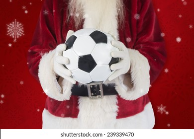 Santa holds a classic football against red snowflake background