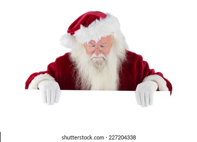 Santa holds a sign and looks down on white background