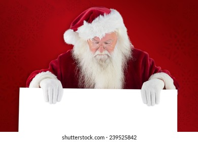Santa holds a sign and looks down against red background
