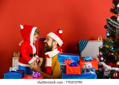 Santa and little assistant among gift boxes near fir tree. Man with beard and cheerful face plays with son on New Year eve. Christmas family opens presents on red background. Christmas eve concept