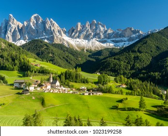 Santa Maddalena village in front of the Geisler or Odle Dolomites Group, Val di Funes, Val di Funes, Trentino Alto Adige, Italy, Europe. Blue sky and green grass, Autumn, 2017