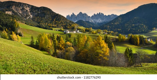 Santa Magdalena village in Val di Funes on the italian Dolomites. Autumnal view of the valley with colorful trees and Odle mountain group on the background. Italy.