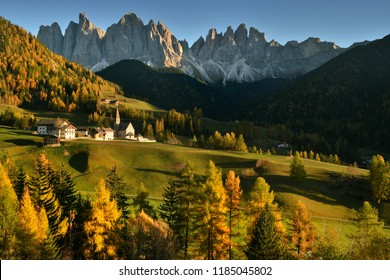 Santa Magdalena village in Val di Funes on the italian Dolomites. Autumnal view of the valley with colorful trees and Odle mountain group on the background in the evening at sunset. Italy.