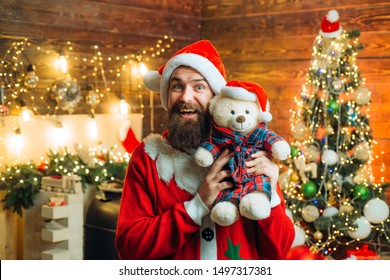 Santa man posing with teddy on vintage wooden background. Happy Santa dressed in winter clothing think about Christmas near Christmas tree. Theme Christmas holidays and winter new year
