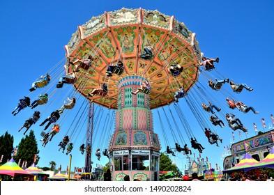 Santa Maria, CA/USA-July 15, 2015: Riders enjoy the Wave Swinger carnival ride at the Santa Barbara County Fair.