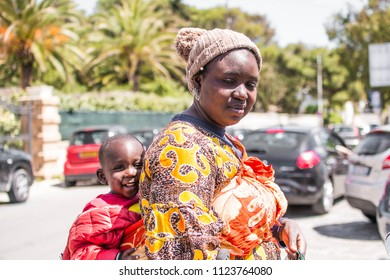 Santa Maria di Leuca,Lecce,Italy-April 25,2016: African mother with baby on her shoulder