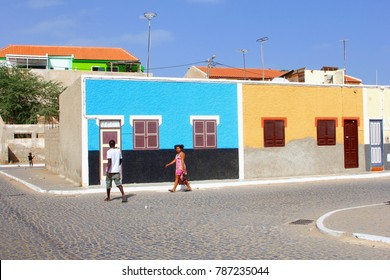 SANTA MARIA, SAL, CAPE VERDE, AFRICA - December 21, 2017. African man and woman with shopping bag walk in neighborhood street with colorful vintage houses in traditional architecture style.