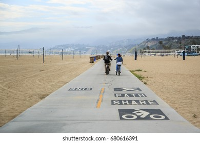 SANTA MONICA, CA: April 6 - Couple of cyclists on a sidewalk at Santa Monica Beach on April 6 2017 in Santa Monica, CA