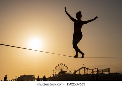 SANTA MONICA, CA - SEPTEMBER 10, 2019: An unidentified woman balances herself while slacklining during sunset at the Original Muscle Beach in Santa Monica Beach.