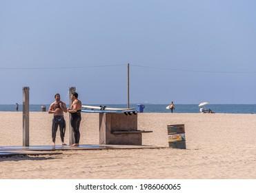 Santa Monica, CA, USA - June 20, 2013: Closeup of couple of male surfers take shower on sandy beach under blue sky.
