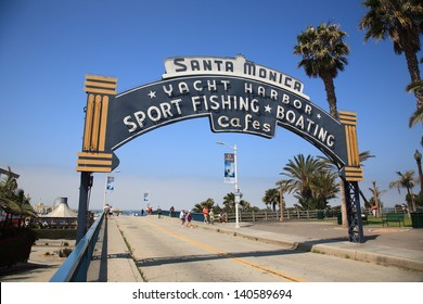 SANTA MONICA, CALIFORNIA - JULY 1: Beach goers stroll under a welcoming arch on July 1, 2012 in Santa Monica, California. The city has 3.5 miles of beach locations and 340 days of sunshine a year.