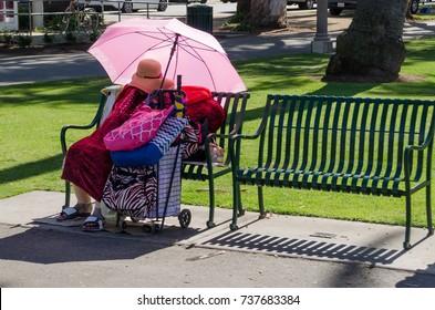 SANTA MONICA, CALIFORNIA, USA, March 16, 2015: Homeless woman with umbrella to block the sun, asleep on a bench in Santa Monica, CA