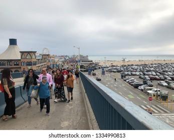 Santa Monica, California/USA - February 27, 2018: Group of migrants walk across bridge near Santa Monica Pier