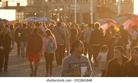 SANTA MONICA, LOS ANGELES CA USA - 19 DEC 2019: Many multiracial people walking on pier. Pedestrians walk, overcrowded seafront promenade. Crowd in golden sun light on broadwalk, sun rays over heads.
