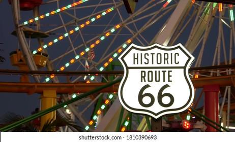 SANTA MONICA, LOS ANGELES, USA - 28 OCT 2019: Iconic road sign glowing, historic route 66. Famous california symbol, pier of pacific ocean resort. Illuminated festive ferris wheel in amusement park.
