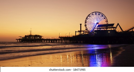 Santa Monica Pier silhouetted against a sunset and reflected in the wet sand of the beach