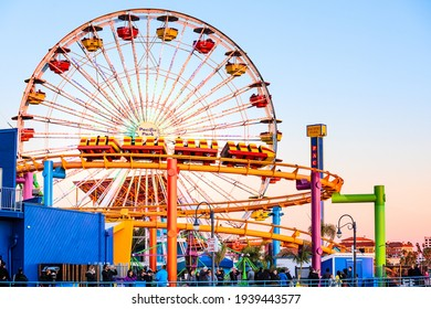 Santa Monica, USA - December 27, 2015: Ferris wheel and roller coaster rides at pier pacific park at sunset with people riding attractions