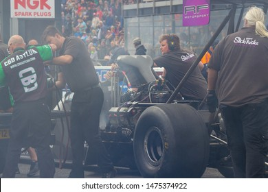 Santa Pod Raceway, UK, May 26 2019.  Top Fuel dragster startup with attendants and spectators. Driver Susanne Callin of Sweden. FIA/FIM The Main Event, European Drag Racing Competition.