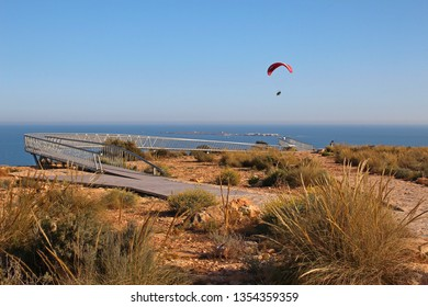 Santa Pola, Alicante Province, Valencia, Spain - 03/25/2019. A paraglider sails by people on the Skywalk viewing platform at the top of the cliff near the lighthouse. Tabarca Island seen beyond.