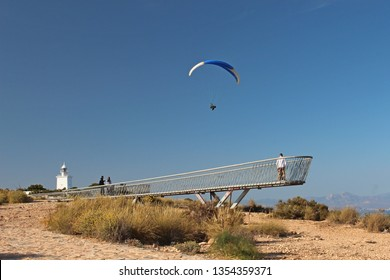 Santa Pola, Alicante Province, Valencia, Spain - 03/25/2019. A paraglider sailing by the Skywalk viewing platform on the top of the cliff near the Santa Pola lighthouse (faro).