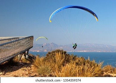 Santa Pola, Alicante Province, Valencia, Spain - 03/25/2019. Two paragliders sailing by the Skywalk viewing platform on the top of the cliff near the lighthouse. In the background is Alicante city.