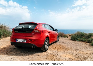 Santa Ponsa, Mallorca, Spain - May 28, 2015: Red car Volvo v40 stands on the edge of a cliff in front of Mediterranean sea. Morro d'en Pere Joan bay, Es Malgrat rocks in Santa Ponsa, Mallorca, Spain.