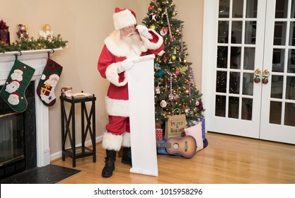 Santa reading his naughty or nice list in a living room decorated for Christmas.