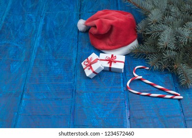 Santa red hat, Gift boxes and colorful present for christmas on blue background. Top view with copy space.