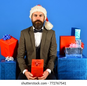 Santa in retro suit presents blue and red gifts. Xmas corporate party concept. Businessman with serious face and stack of boxes. Man with beard holds presents on blue background