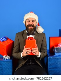 Santa in retro suit presents blue and red gifts. Man with beard holds presents. Christmas gift concept. Businessman with cheerful face and stack of boxes on blue background