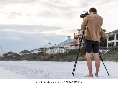 Santa Rosa Beach, Florida with back of young man photographer standing taking picture looking at coastline buildings