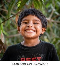 Santa Rosa Guatemala 01-20-2020 portrait of young hispanic boy on tree in Guatemalan village