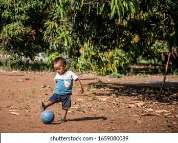 Santa Rosa Guatemala 01-20-2020 young hispanic boy playing with football on dirt soccer field in Guatemala