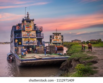 Santa Rosa, Peru - Mar 24, 2018: Sunset over the Amazon river and the cargo boat waiting at the port.