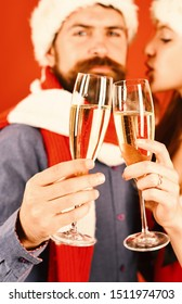 Santa and sexy girl with drinks, close up. Man with beard and woman with happy faces on red background, defocused. Couple in love holds glasses of champagne and kisses. New Year time concept.