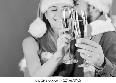 Santa and sexy girl with drinks cuddling. Mister and Missis Claus hold glasses of champagne, closeup. Man with beard and woman with romantic faces on red background, defocused. Christmas party concept
