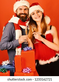 Santa and sexy girl with drinks. Mister and Missis Claus hold glasses of champagne. Man with beard and woman with happy faces on red background. Christmas party concept.