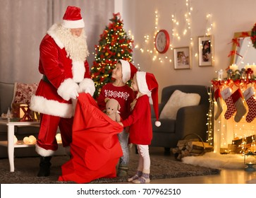 Santa showing presents to cute kids in room with beautiful Christmas decorations
