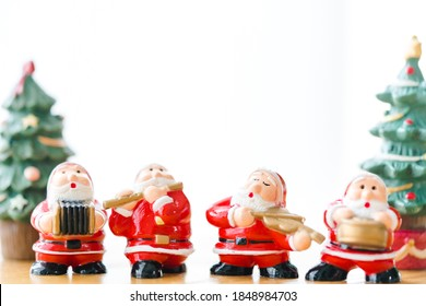 Santa sing a song on Christmas caroling day or Carolers singing outside with snows.Group of Santa claus play music singing carol song on celebration of christmas day in winter time.Holidays music.