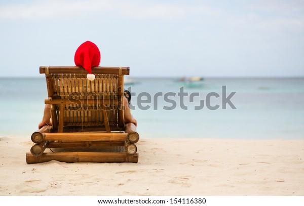 Santa sitting on chaise longue on white sand beach