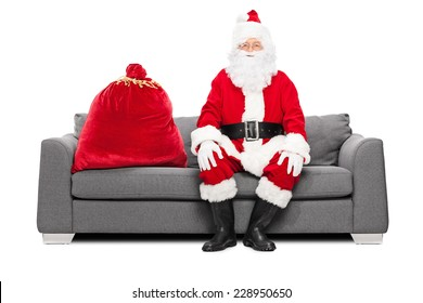 Santa sitting on a sofa with a bag of presents next to him isolated on white background