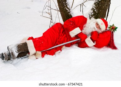 Santa sleeps on a snow near tree
